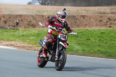 Racing supermoto rider. OSWESTRY, UK - APRIL 27: An unnamed rider competing in the NoraSport UK Supermoto championship accelerates out of a left hand corner at Royalty Free Stock Photo