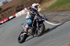 Racing Supermoto rider. OSWESTRY, UK - APRIL 27: An unnamed rider competing in the NoraSport UK Supermoto championship accelerates out of a tight left hand bend Stock Photos