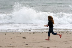 Racing the waves. Child running across the beach stock photos