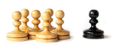 Racism between black and white pawns. On white background Royalty Free Stock Images