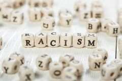 Racism word written on wood block. Word RACISM formed by wood alphabet blocks. On old wooden table Stock Photos