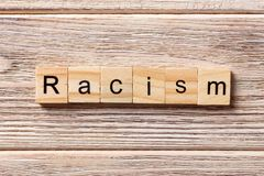 Racism word written on wood block. Racism text on table, concept.  Stock Images