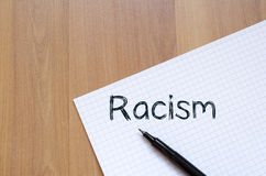 Racism write on notebook. Racism text concept write on notebook with pen Royalty Free Stock Images