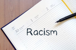 Racism write on notebook. Racism text concept write on notebook with pen Royalty Free Stock Image