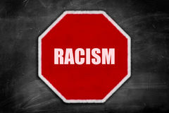 Racism written on  a stop sign on a black chalkboard. With room for print Royalty Free Stock Photo