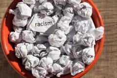 Racisme écrit par papier chiffonné à l'intérieur de la poubelle Boules de papier Photographie stock