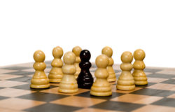 Racist Concept. Concept image of racism with some white chess pawns surrounding a black one Stock Photo
