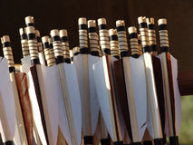 Rack of arrows showing feathers. Rack full of arrows showing white feathers and binding in sunlight stock image