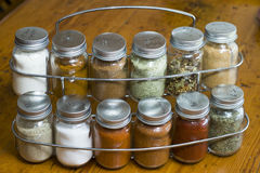 Rack of assorted spices. Assorted spices in glass bottle containers on a wooden table surface Royalty Free Stock Images