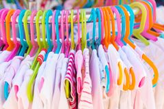 Rack of baby and children used dress, clothes displayed at outdoor hanger market for sale.  royalty free stock photos