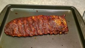 Rack of barbequed pork ribs ready to serve, uncut. And arranged stock photography