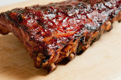 A rack of bbq pork ribs. A full rack barbecue pork back ribs with sauce on a cutting board with a white background Stock Photography
