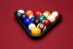 Rack of billiard balls. A full rack of billiard balls on a red table stock image