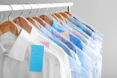 Rack with clean clothes on hangers after dry-cleaning. Against light background stock photography