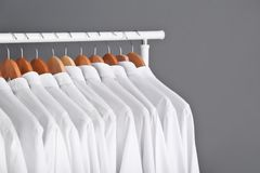 Rack with clean clothes on hangers. After dry-cleaning against grey background Royalty Free Stock Photos