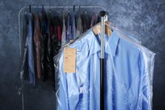 Rack of clean clothes hanging on hangers. At dry-cleaning Stock Photo