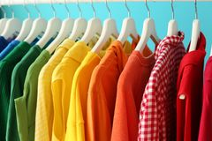 Rack with rainbow clothes on color background. Rack with clothes arranged in rainbow tints on color background royalty free stock photos