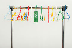 Rack of clothes with empty hangers and a sale sign. Royalty Free Stock Image