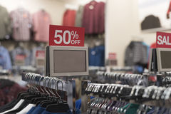 Rack of clothes with 50 % sale sign above Royalty Free Stock Photography