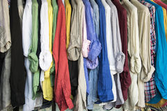 A rack of colorful shirts hanged for sale at the market.  Stock Photos