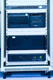 Rack with computers. Mobile rack with computers and ups - blue toned stock photography