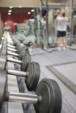 Rack of dumbbells in health club with man lifting weights in background Royalty Free Stock Images