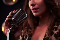 Rack focus of a girl holding a silver vintage microphone. Microphone isolated on spotlights. Classical Vintage Standing Microphone stock image