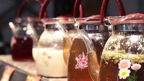 Rack focus shot of decorative glass teapots, variety of herbal tea at festival. Stock footage stock footage