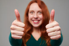 Rack focus on thumbs up given by woman with auburn hair royalty free stock photo