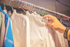 Rack with hangers in a supermarket. Male hand touches some shirt from a lot of clothes and choose some item. Shopping concept royalty free stock photo