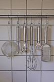 Rack of kitchen utensils. On white tiled background Royalty Free Stock Image