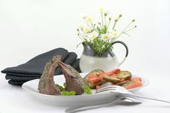 Rack of lamb. Serving platter for two with rack of lamb, roasted fingerling potatoes and carrots garnished with thyme and parsley royalty free stock photos