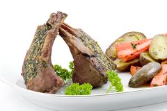 Rack of lamb. Serving platter for two with rack of lamb, roasted fingerling potatoes and carrots garnished with thyme and parsley Royalty Free Stock Photo
