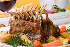 Rack of Lamb. (ribs) with Rosemary garlic dressing, garnished with baby carrots, potatoes and rosemary sprigs. Dinner settings Royalty Free Stock Images