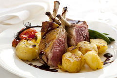 Rack of Lamb Dinner. With crushed roasted potatoes, cherry vine tomatoes, baby green beans and a balsamic jus Royalty Free Stock Images