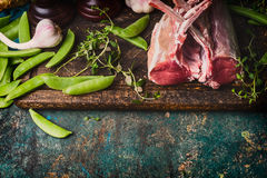 Rack of lamb with green pea pods, cooking preparation on rustic background, top view Stock Photography