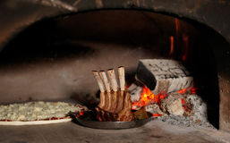 Rack of lamb and oizza in oven Royalty Free Stock Photography