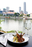 Rack of lamb with view. Table setting for a meal of rack of lamb, overlooking a river and landscape view Stock Photography