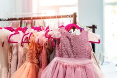 Rack with many beautiful holiday dresses for girls on hangers at children fashion showroom indoor. Kid girl dress hire studio for stock images