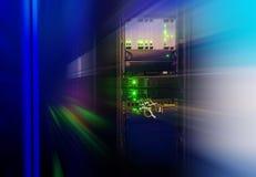 Rack med telekommunikationnätverksutrustning i datorhallen med suddighet royaltyfria bilder