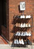Shoe Rack Outside Shoe Store. Rack of men and women shoes on sale outside shoe store royalty free stock photos