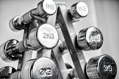 Rack with metal dumbbells. A rack with metal dumbbells Royalty Free Stock Photography