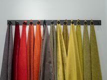 Rack with multiple colors and materials of sample fabrics royalty free stock photos
