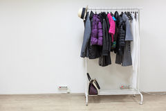 Rack with outerwear standing on floor of white hallway room, copyspace Stock Photography