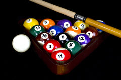 Rack of Pool Balls. Pool balls inside of wooden rack against black background with cue stick Stock Image