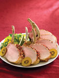 Rack of pork crusted with pepper corns with kiwis Stock Images