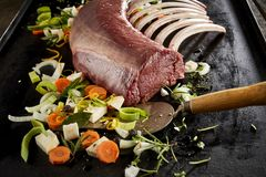 Rack of ribs grilling on hot plate with vegetables stock photo