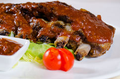 Rack of Saucy Barbecue Pork Ribs on Plate Royalty Free Stock Image