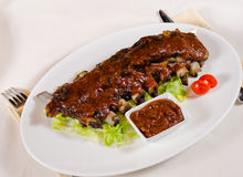 Rack of Saucy Barbecue Pork Ribs on White Plate. Served in Restaurant Stock Image