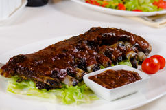 Rack of Saucy Barbecue Pork Ribs on White Plate Stock Images